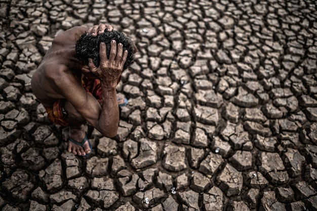 An elderly man sat bent his knees at a dry floor and his hands held his head, global warming Free Photo