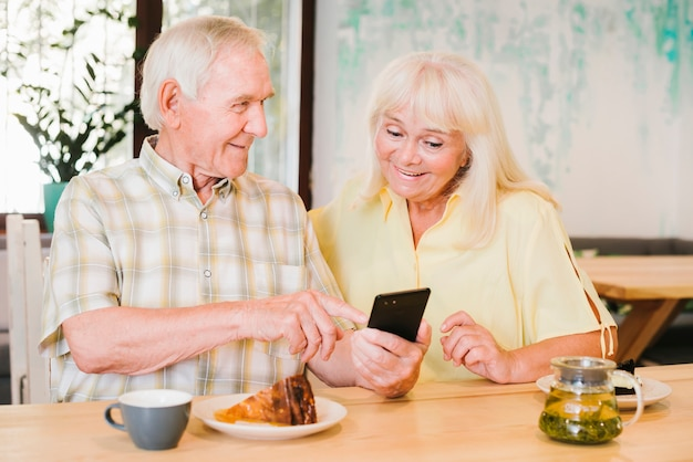 Elderly man showing smartphone to woman Free Photo