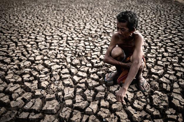 Un uomo anziano seduto abbracciando le ginocchia si chinò sulla terra sterile, il riscaldamento globale Foto Gratuite