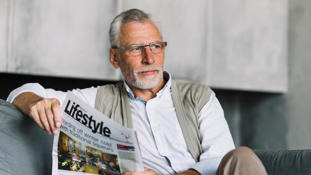 An elderly man sitting on sofa holding newspaper in his hand looking away Free Photo