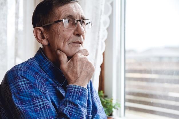 Пожилой мужчина, стоящий у окна Premium Фотографии