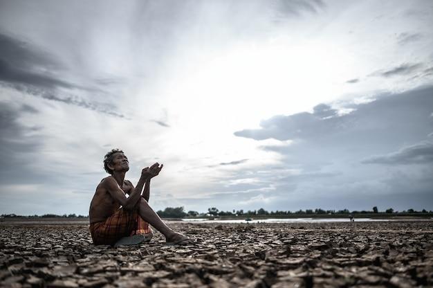 Un uomo anziano era seduto a chiedere pioggia durante la stagione secca, il riscaldamento globale Foto Gratuite
