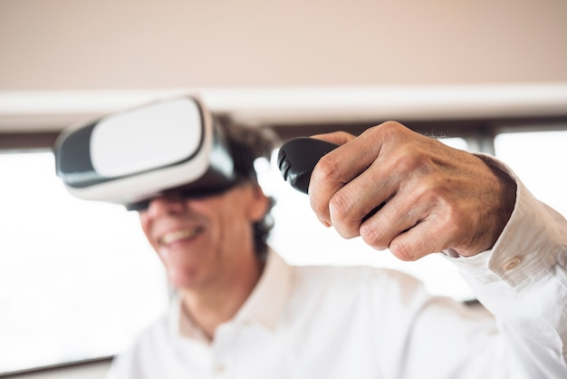 An elderly man wearing virtual reality goggles using remote control Free Photo