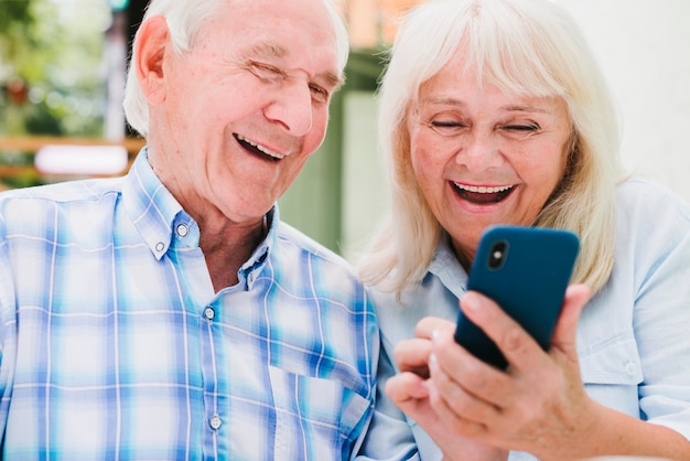 Elderly man and woman using smartphone smiling Free Photo