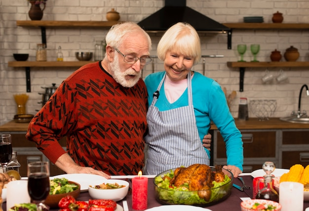 Elderly married couple looking at the cooked turkey Free Photo