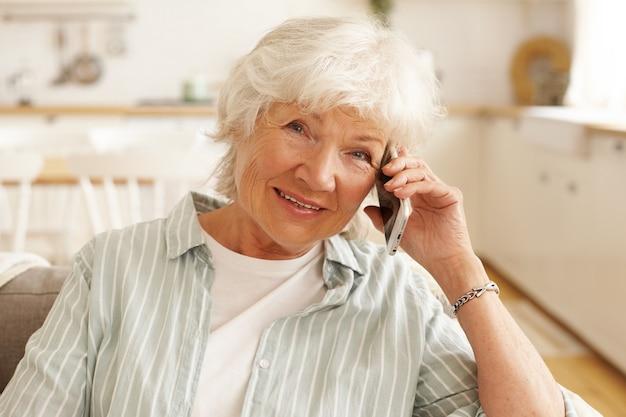 Anziana donna europea matura in camicia a righe avente conversazione telefonica tramite applicazione online utilizzando la connessione internet wireless gratuita ad alta velocità a casa, guardando con un sorriso allegro Foto Gratuite