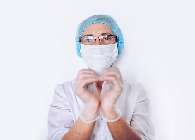 Elderly mature woman doctor or nurse showing heart sign in a white medical coat, gloves, face mask wearing personal protective equipment isolated. healthcare and medicine concept. covid-19 pandemic Premium Photo