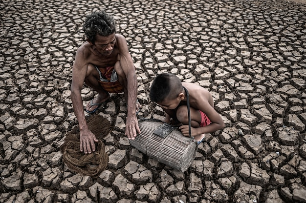 Elderly men and boy find fish on dry ground, global warming Free Photo