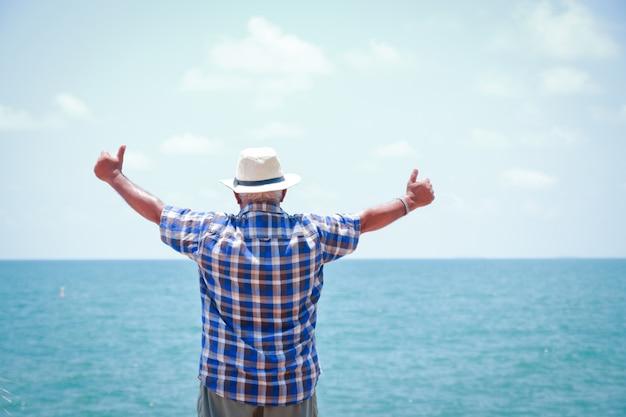 Los ancianos vienen a visitar el mar. de pie, girando hacia atrás, extendiendo ambos brazos, haciendo manos, pulgares arriba, complaciendo Foto Premium