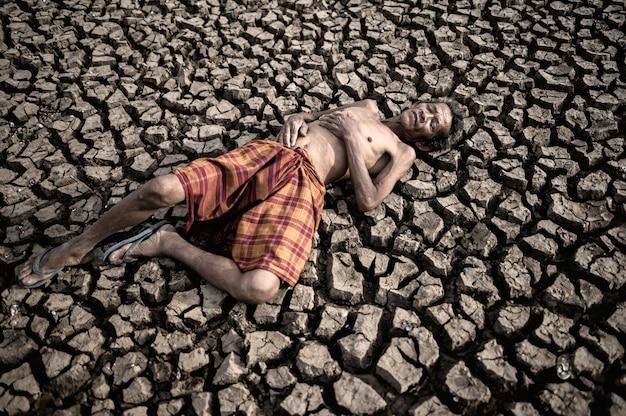 Gli uomini anziani giacciono distesi, le mani appoggiate sulla pancia su un terreno asciutto e screpolato, il riscaldamento globale Foto Gratuite