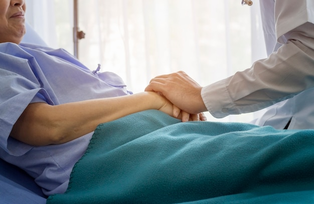 Elderly patient care concept; asian doctor is taking care elderly patient woman in hospital. Premium Photo