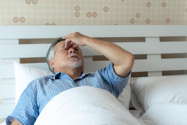 Elderly patients in bed, asian senior man patients headache hands on forehead. Premium Photo