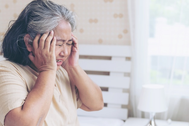 Elderly patients in bed, asian senior woman patients headache hands on forehead - medical and healthcare concept Free Photo