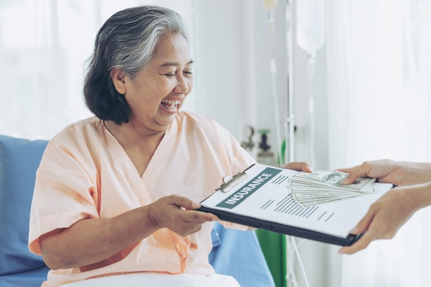 Elderly patients injury  woman on patient's bed in hospital  holding us dollar bills feel happy from getting insurance money from insurance companies Free Photo