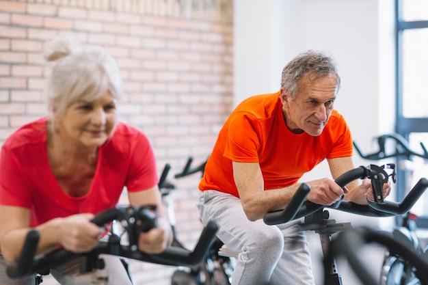 Elderly people on stationery bike Free Photo