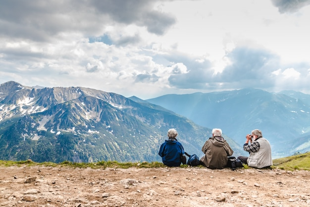 Elderly people with backpacks are sitting on the ground high in the mountains Premium Photo