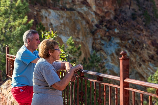 An elderly or retired couple leaning on railings looking out to mines Premium Photo