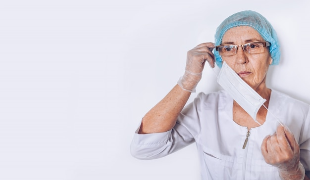 Elderly sad tired mature woman doctor or nurse in a white medical coat, gloves, puts on face mask wearing personal protective equipment isolated. healthcare and medicine concept. covid-19 pandemic Premium Photo