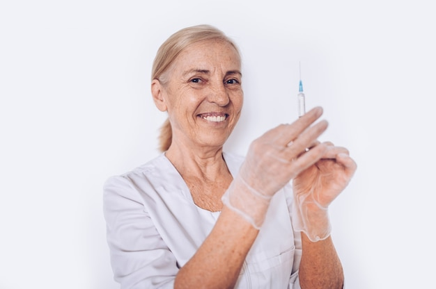 Elderly senior smiling woman doctor or nurse with syringe in a white medical coat and gloves wearing personal protective equipment isolated. healthcare and medicine concept. covid-19 pandemic crisis Premium Photo