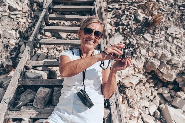 海岸で写真を撮って歩く高齢者シニア旅行バックパッカー成熟した女性観光客 Premium写真