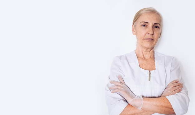 Elderly smiling mature woman doctor or nurse crossed arms in a white medical coat, gloves,  wearing personal protective equipment isolated on white background. healthcare and medicine concept. Premium Photo