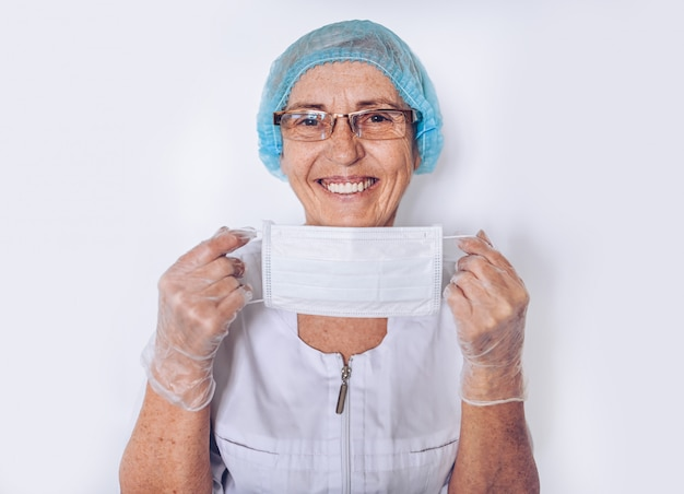 Elderly smiling mature woman doctor or nurse in a white medical coat, gloves, puts on face mask wearing personal protective equipment isolated. healthcare and medicine concept. covid19 pandemic crisis Premium Photo