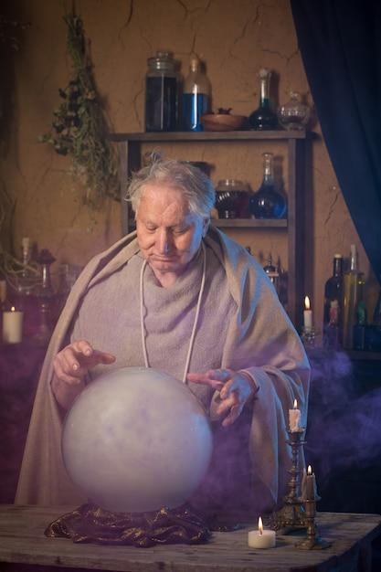 水晶玉を持つ高齢者の魔法使い Premium写真