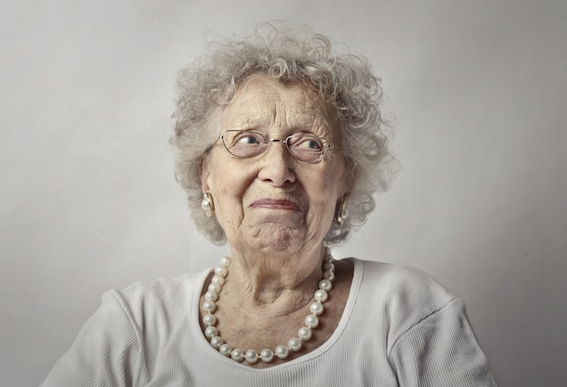 Elderly woman against a white wall with a worried look on her face Free Photo