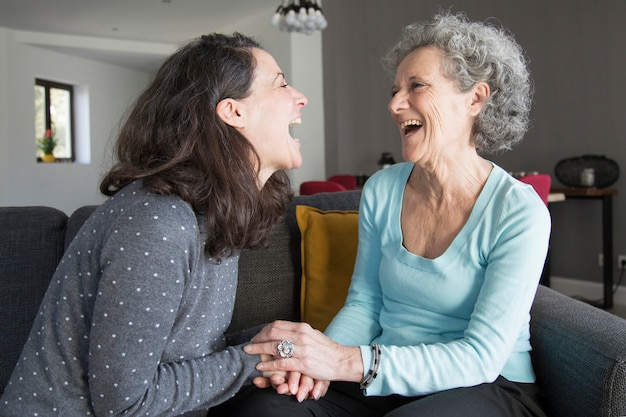 Elderly woman and daughter laughing and holding hands Free Photo