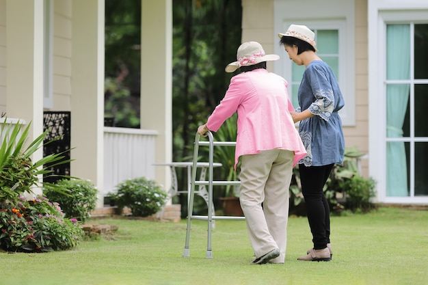 Elderly woman exercise walking in backyard with daughter Premium Photo