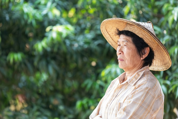 Elderly woman a farmer smiling and holding  in garden. Free Photo