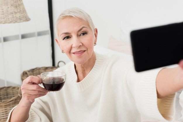 Elderly woman holding coffee cup and taking selfie Free Photo