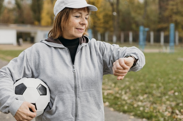 Donna anziana tenendo il calcio e guardando il suo orologio all'aperto Foto Gratuite