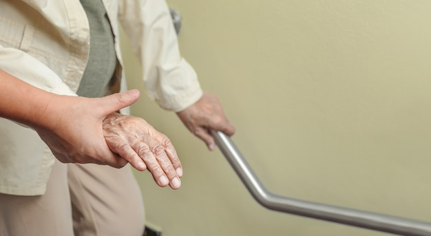 Elderly woman holding on handrail with caregiver Premium Photo