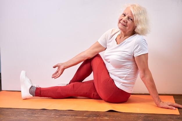 一人で自宅で体を伸ばして、床で運動をしているスポーティーな服を着た年配の女性 Premium写真