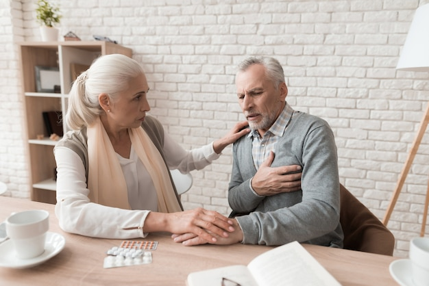 Elderly woman is worried because of pain in husband's heart. Premium Photo