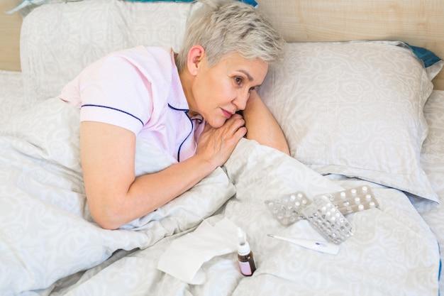 Пожилая женщина лежит на кровати с таблетками Premium Фотографии