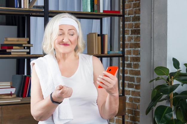 Elderly woman measures pulse by phone Premium Photo