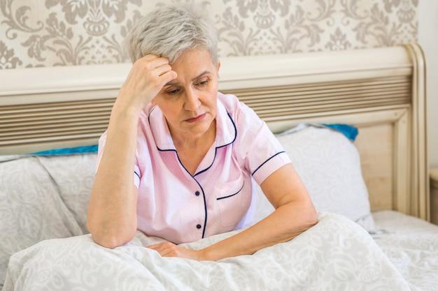 Пожилая женщина на кровати в постели под одеялом Premium Фотографии
