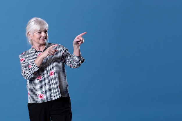 Elderly woman pointing to her left Free Photo