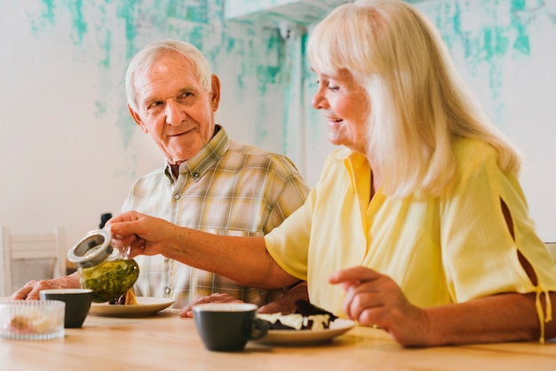 Elderly woman pouring tea to gray haired man Free Photo