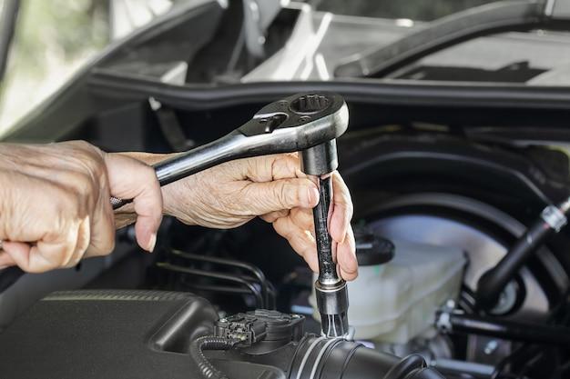 Elderly woman repairing her car Premium Photo