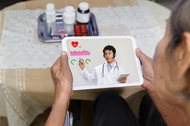 高齢者の女性は、タブレットコンピューターで医師とオンライン相談を持つ自宅で座っています。 Premium写真