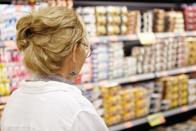 Donna anziana in supermercato Foto Gratuite
