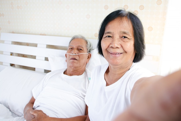 An elderly woman taking a picture with her husband who is suffering from lung disease and respiratory disease in bed in the bedroom. concept of care, encouragement and prevention of coronavirus Premium Photo