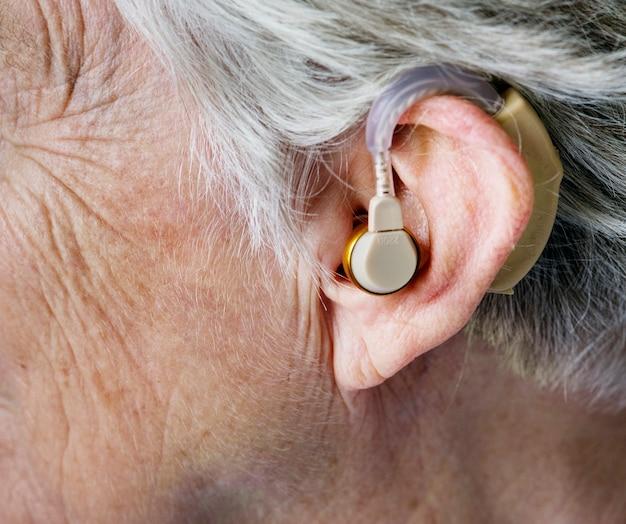 Elderly woman wearing a hearing aid Free Photo