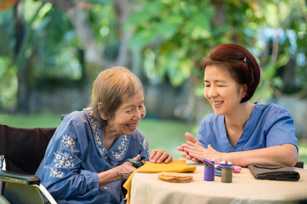 Пожилая женщина с попечителем трудовой терапии Premium Фотографии