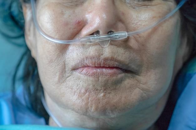 彼女の呼吸を助けるために鼻呼吸チューブを持つ高齢者の女性 Premium写真