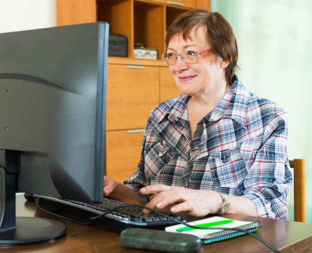 Elderly woman working with computer Free Photo