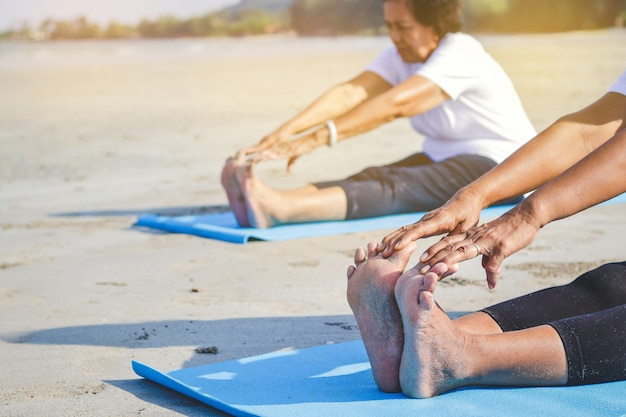 Elderly women exercising at the beach by the sea fresh air, strong body Premium Photo